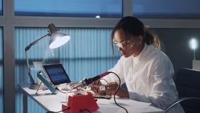 Cierre medio para arriba del ingeniero electrónico afroamericano en vidrios protectores que comprueba la placa madre con el multí almacen de video