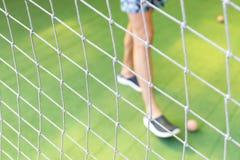Cierre neto del fútbol para arriba en campo de fútbol borroso de la hierba verde y los pies masculinos que juegan un pequeño fond foto de archivo libre de regalías