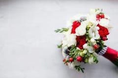 Cierre nupcial del ramo para arriba rosas rojas y blancas, fresia, brunia adornadas en la composición Fotos de archivo