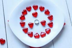 Cierre para arriba anillo y corazones rojos en una placa blanca Fotos de archivo