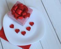 Cierre para arriba caja de regalo y corazones rojos en una placa blanca Imagen de archivo