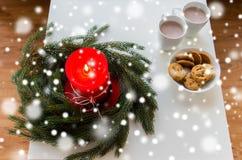 Cierre para arriba de la guirnalda de la Navidad con la vela en la tabla Foto de archivo