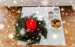Cierre para arriba de la guirnalda de la Navidad con la vela en la tabla Imagenes de archivo