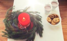 Cierre para arriba de la guirnalda de la Navidad con la vela en la tabla Imagen de archivo