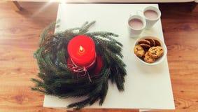 Cierre para arriba de la guirnalda de la Navidad con la vela en la tabla Fotografía de archivo libre de regalías