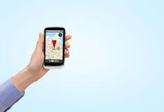 Cierre para arriba de la mano con el mapa del navegador de los gps del smartphone Fotos de archivo