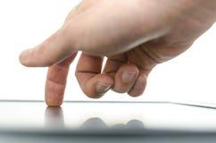 Ciérrese para arriba de la mano masculina usando un dispositivo de la pantalla táctil Fotos de archivo libres de regalías