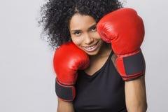 Cierre para arriba de la mujer alegre en soporte de la lucha con los guantes de boxeo rojos Imagen de archivo