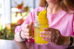 Cierre para arriba de la mujer feliz que bebe el cóctel amarillo con la rebanada anaranjada en el café - bebidas, gente y concept imagen de archivo libre de regalías