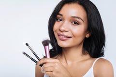 Cierre para arriba de la mujer hermosa que presenta con los cepillos del maquillaje Fotos de archivo libres de regalías