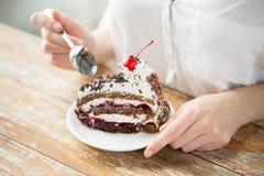 Cierre para arriba de la mujer que come la torta de la cereza del chocolate Imagen de archivo
