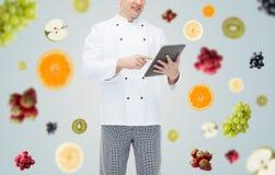 Cierre para arriba de la PC masculina feliz de la tableta de la tenencia del cocinero del cocinero Foto de archivo libre de regalías