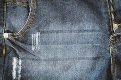 Cierre para arriba de la textura azul de los pantalones de la mezclilla del dril de algodón viejo con el CCB del bolsillo Foto de archivo libre de regalías