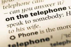 Cierre para arriba de la vieja página inglesa del diccionario con palabra en el teléfono Fotografía de archivo
