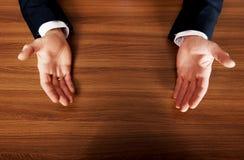Cierre para arriba de las manos abiertas del hombre de negocios en el escritorio Foto de archivo libre de regalías