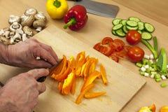 Cierre para arriba de las manos de los cocineros que cortan un paprika amarillo Foto de archivo libre de regalías