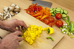 Cierre para arriba de las manos de los cocineros que cortan un paprika en cuadritos amarillo Fotografía de archivo