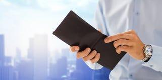 Cierre para arriba de las manos del hombre de negocios que sostienen la cartera abierta Fotografía de archivo