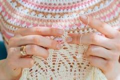 Cierre para arriba de las manos del ` s de la artesana que hacen punto el vestido con el ganchillo Trabajo femenino con el cordón foto de archivo