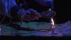 Cierre para arriba de las manos femeninas con una lupa sobre el mapa del tesoro, 4k almacen de video