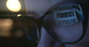 Cierre para arriba de los ojos de la mujer joven en los vidrios que practican surf en Internet almacen de video