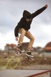 Cierre para arriba de los pies de los skateres mientras que funcionamiento activo patinador del adolescente del truco tirado en e Imagen de archivo
