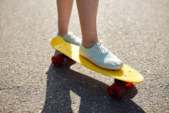 Cierre para arriba de los pies femeninos que montan el monopatín corto Foto de archivo