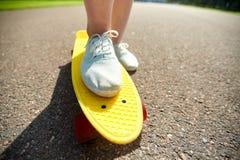 Cierre para arriba de los pies femeninos que montan el monopatín corto Fotografía de archivo libre de regalías