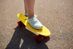 Cierre para arriba de los pies femeninos que montan el monopatín corto Foto de archivo libre de regalías