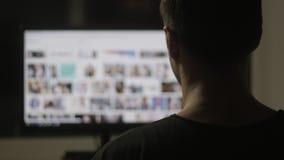 Cierre para arriba de los sitios web que practican surf del hombre joven en Internet en la fuerza en casa almacen de metraje de vídeo