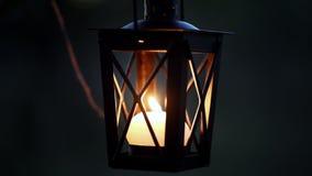 Cierre para arriba de luces de la mano de la mujer a la vela en linterna de la vela en la rama