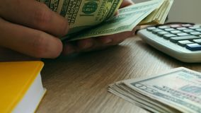 Cierre para arriba de manos eso que cuenta billetes de dólar dinero en una tabla metrajes