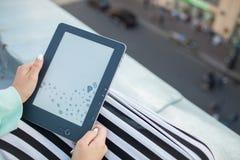 Cierre para arriba de manos femeninas con el control de la manicura un eBook Muchacha que lee un libro en el tejado del edificio Imágenes de archivo libres de regalías