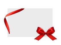 Cierre para arriba de un arco rojo de la cinta en el fondo blanco Imagenes de archivo