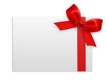 Cierre para arriba de un arco rojo de la cinta en el fondo blanco Imágenes de archivo libres de regalías