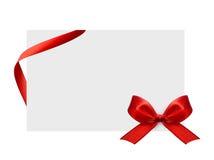 Cierre para arriba de un arco rojo de la cinta en el fondo blanco Fotografía de archivo