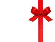 Cierre para arriba de un arco rojo de la cinta en el fondo blanco Fotografía de archivo libre de regalías