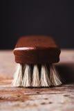 Cierre para arriba de un cepillo del brillo del zapato en un fondo rústico Fotografía de archivo libre de regalías