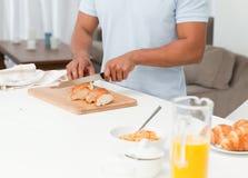 Cierre para arriba de un pan del corte del hombre durante el desayuno Imagen de archivo libre de regalías