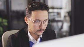 Cierre para arriba de un trabajo del hombre de negocios con el ordenador en la oficina metrajes