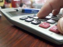 Cierre para arriba de una entrega una calculadora Fotos de archivo libres de regalías