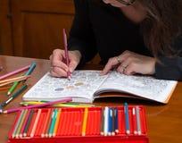Cierre para arriba de una mujer que colorea un dibujo del lanzamiento de la tensión Fotografía de archivo