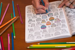 Cierre para arriba de una mujer que colorea un dibujo del lanzamiento de la tensión Imagen de archivo libre de regalías