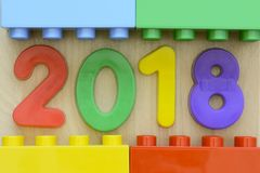 Cierre para arriba del año 2018 en los números plásticos coloridos rodeados por los bloques plásticos del juguete Foto de archivo libre de regalías