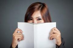 Cierre para arriba del control asiático de la muchacha del negocio un libro Imagen de archivo