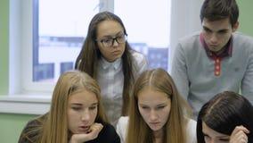 Cierre para arriba del equipo del negocio que prepara la presentación de su inicio Dos de pelo rubio jovenes y muchachas oscuro-c almacen de video