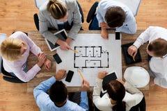 Cierre para arriba del equipo del negocio que se sienta en la tabla Fotos de archivo