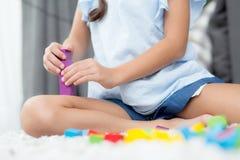Cierre para arriba del niño de la mano que juega con el bloque plástico colorido en el piso Imagen de archivo