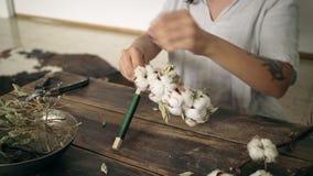 Cierre para arriba del trabajo de manos femenino sobre la guirnalda del algodón almacen de metraje de vídeo