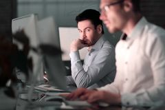 Cierre para arriba dos colegas que trabajan en la noche en la oficina imagen de archivo